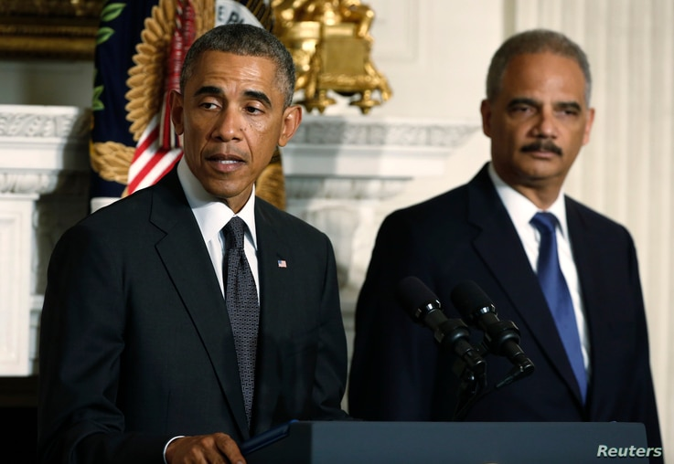U.S. President Barack Obama (L) announces the resignation of  Attorney General Eric Holder (R) in the White House State Dining Room in Washington, Sept. 25, 2014.