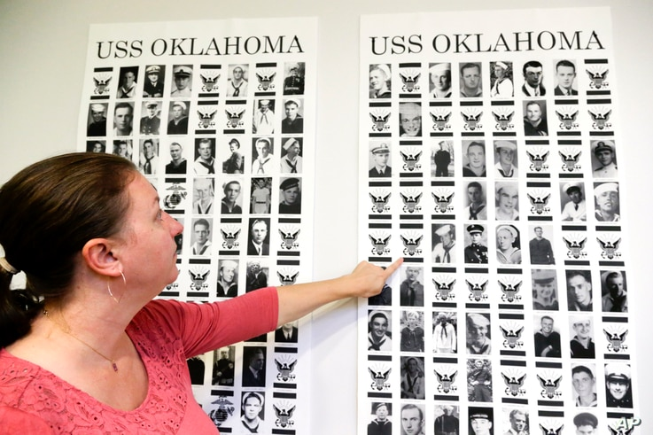 In this Sept. 18, 2018 photo, Dr. Carrie Brown, forensic anthropologist and director of the USS Oklahoma Project at the Defense POW/MIA Accounting Agency (DPAA) Identification laboratory, points to images on posters showing the names and photos of th...