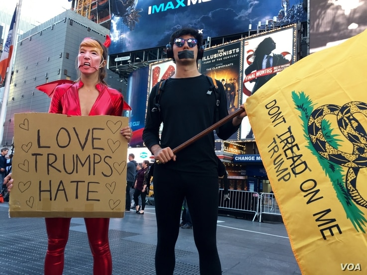 Lucinda Aragon (left), dressed in a costume with a Donald Trump mask, said she thinks the Republican candidate's policies are divisive, and she said she is supporting Hillary Clinton, in Times Square, New York, Nov. 8, 2016. (R. Taylor/VOA)