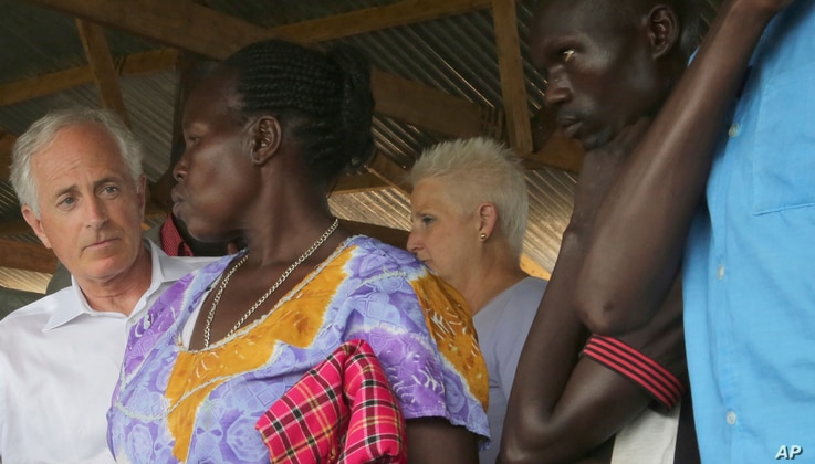 U.S. Sen. Bob Corker, left, speaks with a woman who has recently arrived from South Sudan, at a registration center in northern Uganda for South Sudanese refugees, April 14, 2017.