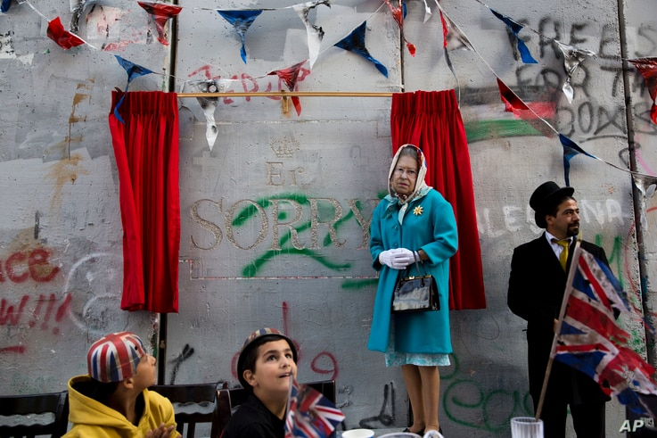 A woman wearing a mask of Queen Elisabeth stands next to the message by the elusive artist Banksy on the anniversary of the Balfour Declaration Bethlehem, West Bank, Nov. 1, 2017. The Balfour Declaration, Britain's promise to Zionists to create a Jew...