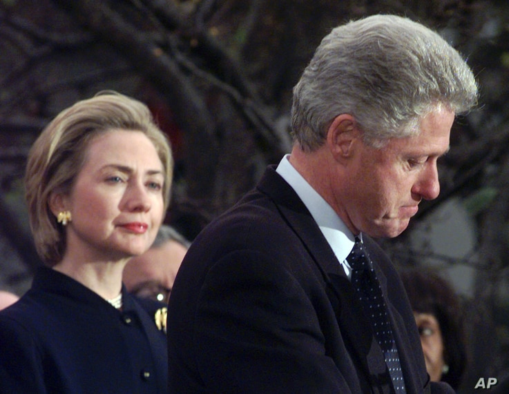 FILE - Then first lady Hillary Clinton watches her husband, President Bill Clinton, pause as he thanks those Democratic members of the House of Representatives who voted against his impeachment, Dec. 19, 1998. Clinton was impeached by the House but l...