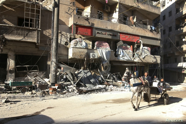 People ride a cart pulled by a horse near the damaged al-Hakeem hospital, in the rebel-held besieged area of Aleppo, Syria, Nov. 19, 2016. Western governments and the United Nations have framed the Aleppo onslaught as a vast humanitarian crisis.
