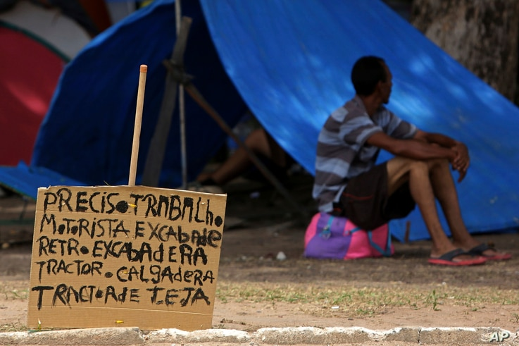 """In this March 11, 2018 photo, a sign that reads in Portuguese: """"I need work. Tractor driver. Excavator."""" near a Venezuelan migrant outside his tent in Simon Bolivar Square where Venezuelans have set up tents."""