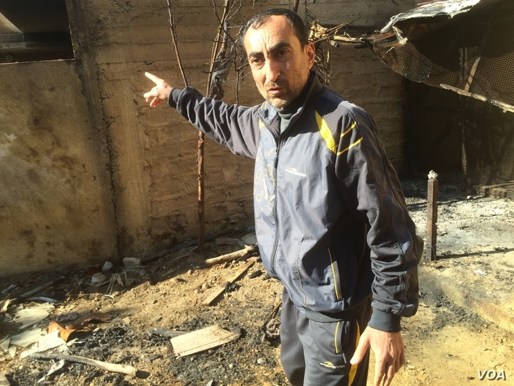 Wissam Rashid points to what looks like oil residue after his home, now condemned, was bombed, spraying a foul-smelling oily substance on his home and garden in eastern Mosul, Iraq, March 8, 2017.