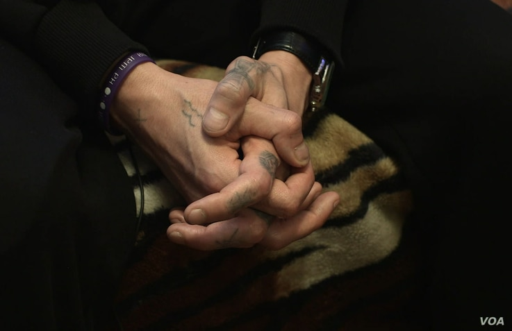 A Russian drug addict holds his hand together during a rehabilitation session at the Vershina-Navigator Foundation's rehabilitation center outside Moscow. The number of Russians infected with HIV is growing and has surpassed 1 million, according to g...