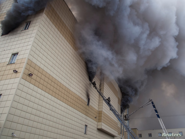 Members of the Emergency Situations Ministry work to extinguish a fire in a shopping mall in the Siberian city of Kemerovo, Russia.