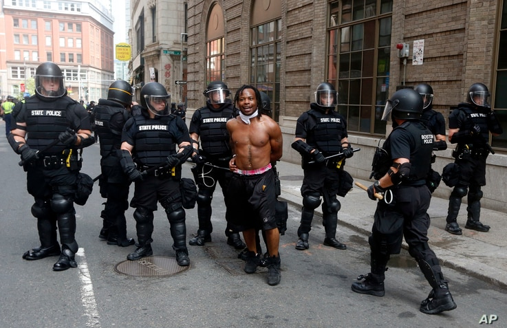 """Police escort away a counterprotester near a """"Free Speech"""" rally staged by conservative activists, Aug. 19, 2017, in Boston."""