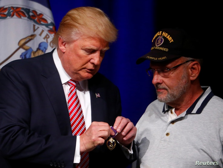 Republican U.S. Presidential nominee Donald Trump talks to Lt. Col. Louis Dorfman, who gave Trump his Purple Heart, during a campaign event at Briar Woods High School in Ashburn, Virginia, Aug. 2, 2016.