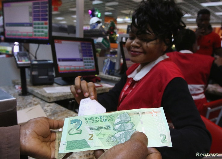 A till operator poses with new bond notes at a supermarket in Harare, Nov. 28, 2016.