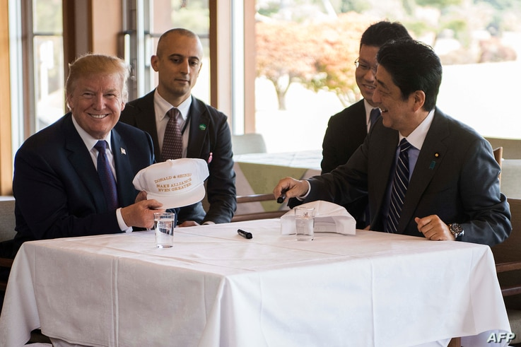 "US President Donald Trump speaks with Japan's Prime Minister Shinzo Abe during a luncheon at the Kasumigaseki Country Club Gold Course in Tokyo, Nov. 5, 2017. The president and prime minister signed white hats reading ""Donald and Shinzo Make Allian..."