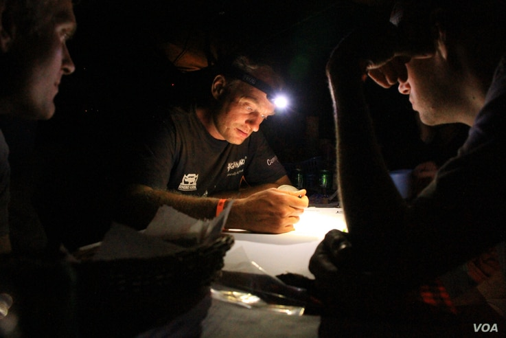 Henrik Rasmussen and other members of Car 54, the Danish team, plot the next day's Rhino Charge by the light of a head lamp and bonfire, June 1, 2012. (VOA Photo/Jill Craig)