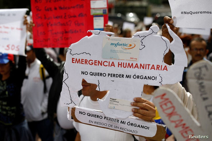"Reinaldo Olivares, a kidney transplanted patient, holds a placard with the shape of the map of Venezuela that reads, ""Humanitarian emergency. I do not want to lose my organ,"" during a protest against medicinal shortages in Caracas, Venezuela, Feb. 8,..."