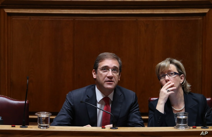 Portuguese Prime Minister Pedro Passos Coelho and Finance Minister Maria Luis Albuquerque, right, look at a wall clock Tuesday, Nov. 10, 2015, during the debate of the government's four-year policy program at the Parliament in Lisbon.