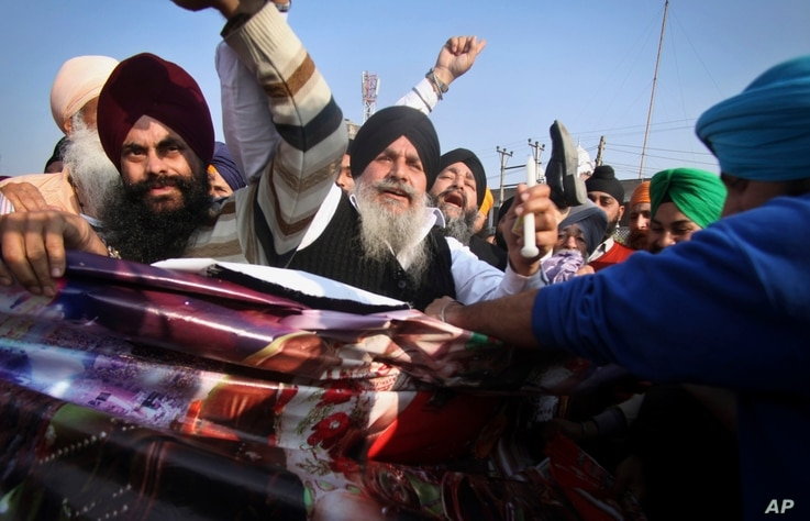 "FILE - Sikh protesters hold a poster of Indian religious sect Dera Sacha Sauda chief Baba Ram Rahim Singh's debut film ""MSG: The Messenger of God"" in Jammu, India, Feb. 13, 2015."