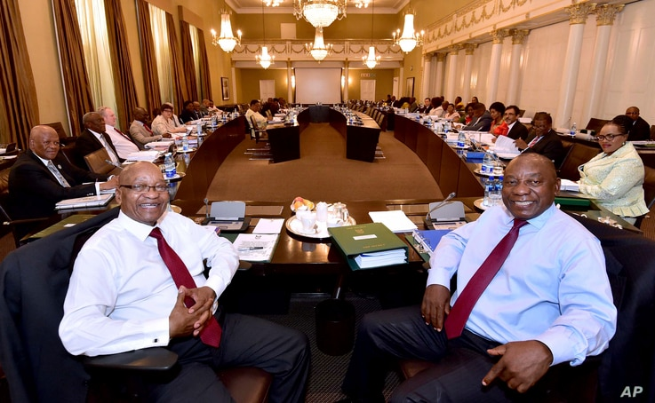 In this photo supplied by the South African Government Communications and Information Services (GCIS) South African President Jacob Zuma, left, and Deputy President Cyril Ramaphosa, right, with minsters and deputy ministers at a scheduled routine mee...