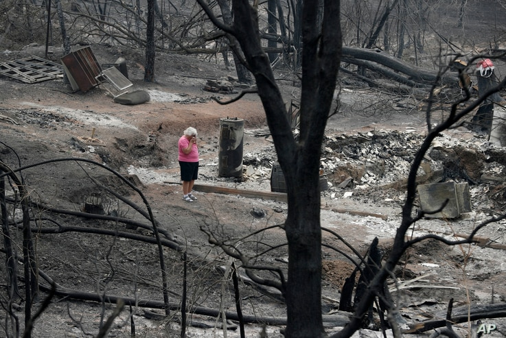 """Loretta Root wipes her eyes while visiting the remains of her home in the Keswick area burned in the Carr Fire, Aug. 9, 2018, in Redding, Calif. """"It's hard to see this,"""" Root says of her family home. Several of Root's family members living nearby als..."""