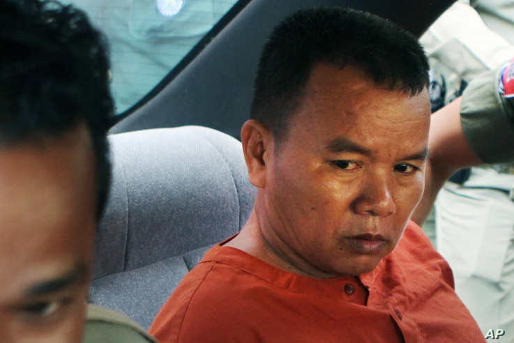 Yem Chrin, left, an unlicensed medical practitioner, sits in a car as escorting by prison guards after a verdict announcing of the Battambang provincial court in Battambang province, northwest of Phnom Penh, Cambodia, Thursday, Dec. 3, 2015. The Camb...