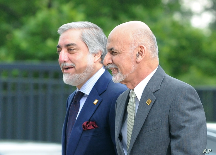FILE - Afghanistan's President Ashraf Ghani, right, and Chief Executive Abdullah Abdullah arrive for sessions of the second day of the NATO Summit, in Warsaw, Poland, Saturday, July 9, 2016.