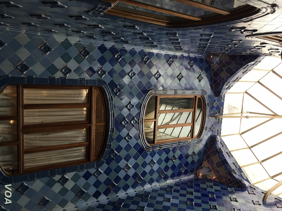 A large skylight illuminates the dark blue tiles of the upper floor of Casa Batllo, in Barcelona.