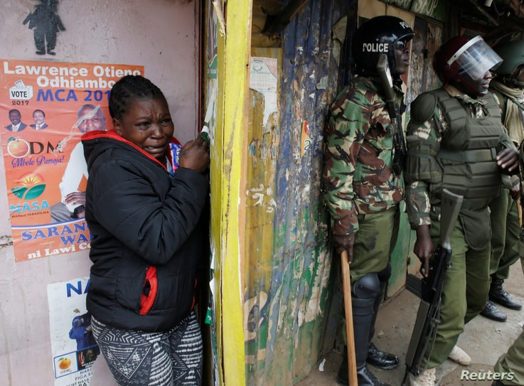 A woman cries as she takes cover during clashes between supporters of opposition leader Raila Odinga and policemen in Kibera slum, Nairobi, Kenya, Aug. 12, 2017.