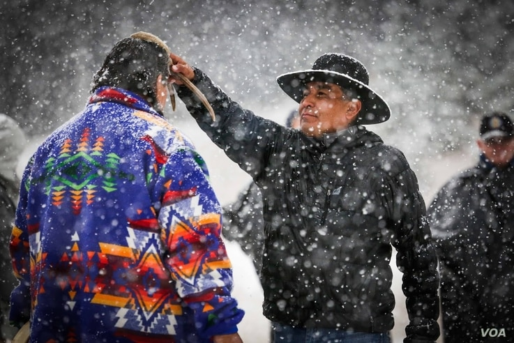 Photo shows cultural advisor Craig Falcon (R) blessing Roger Vielle, both members of Blackfeet tribe, during a Vietnam veterans retreat on the Blackfeet Reservation in Montana, September 2017. Courtesy, Wingspan Media Productions.