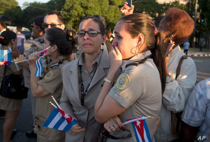 Officials from the costumes ministry react as , placed in a small coffin covered by a Cuban flag, the ashes of Cuban leader Fidel Castro are driven along Revolution Square in Havana, Cuba, Nov. 30, 2016.
