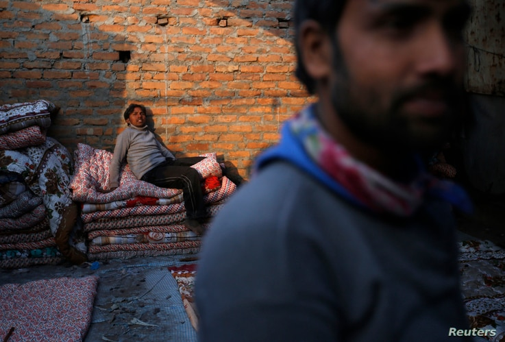 FILE - A migrant worker from India sits in the sun as he takes a break while making blankets from recycled cotton in Kathmandu, Nepal Dec. 22, 2015.