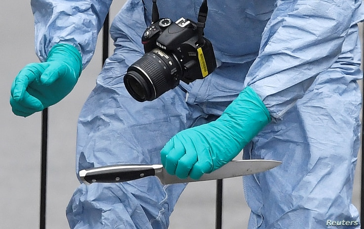 FILE - A forensic investigator recovers a knife after man was arrested on Whitehall in Westminster, central London, April 27, 2017.