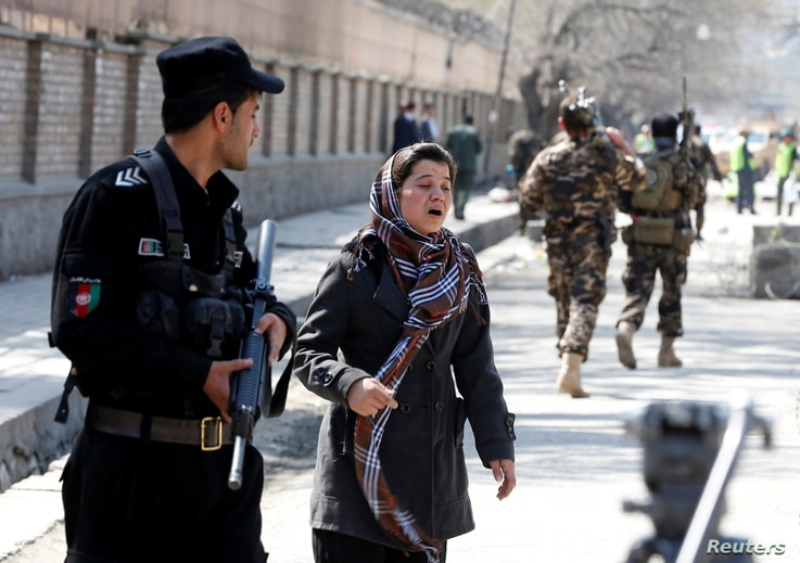 An Afghan woman seeks for her relative at the site of a suicide bombing in Kabul, Afghanistan, March 21, 2018.
