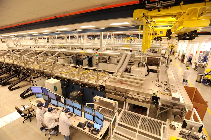 FILE - Workers man a control bank at Solyndra's solar panel factory on in Fremont, Calif., Oct. 6, 2010.