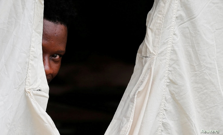 A Haitian refugee peeks out of the window of a tent set up by Canadian Armed Forces near the border in Lacolle, Quebec, Aug. 10, 2017.