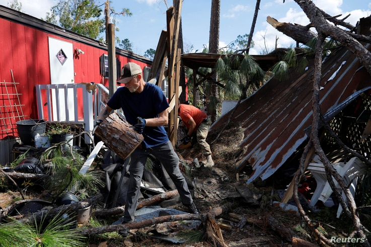 50 Star Search and Rescue team member Robert Pepper clears debris from the yard of Yvette Beasley after Hurricane Michael in Fountain, Florida, Oct. 17, 2018.