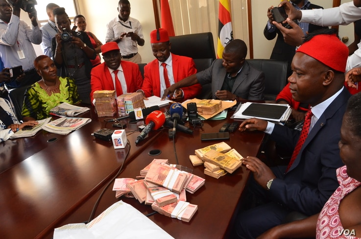 Members of the Ugandan opposition in Parliament address journalists as they return money given to them for consultations on the amendment of the Age Limit Bill, Oct. 25, 2017. (Halima Athumani for VOA)