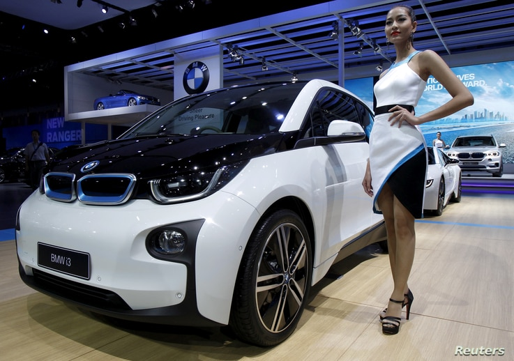 FILE - A model poses beside a BMW i3 during a media presentation during the 36th Bangkok International Motor Show in Bangkok, Thailand, March 24, 2015.