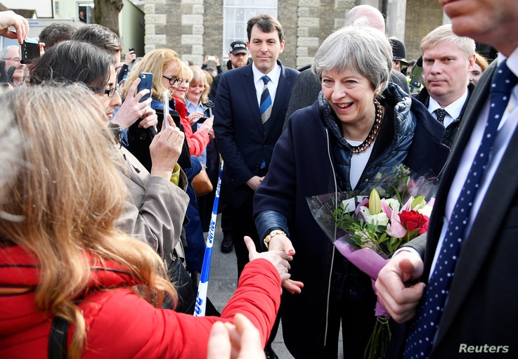 Britain's Prime Minister Theresa May greets people after visiting the scene where former Russian intelligence officer Sergei Skripal and his daughter Yulia were found after they were poisoned with a nerve agent, in Salisbury, Britain, March 15, 2018....