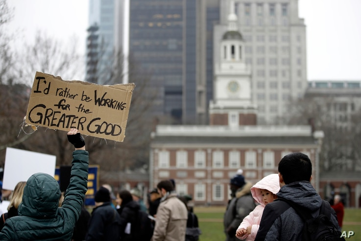 Furloughed federal worker Meghan Powell, holding sign on left, demonstrates with others against the partial government shutdown in view of Independence Hall in Philadelphia, Jan. 8, 2019.