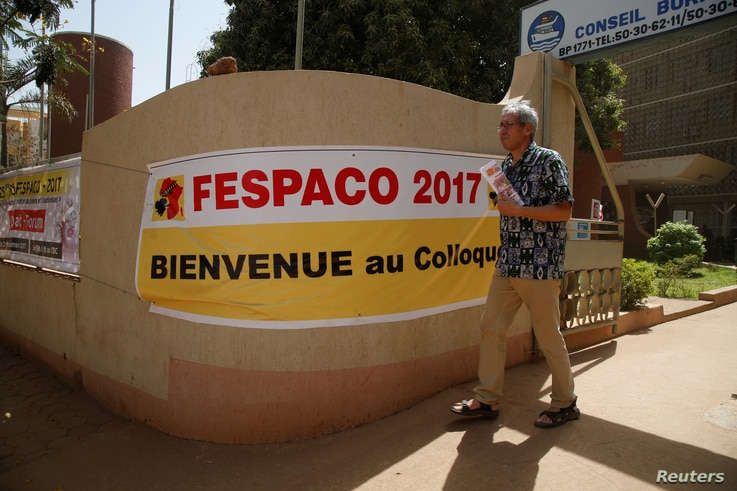 The Tunisian filmmaker Mohamed Challouf walks as he passes a banner during the Panafrican Film and Television Festival (FESPACO) in Ouagadougou, Burkina Faso, March 3, 2017.