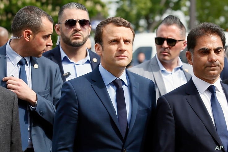French centrist presidential candidate Emmanuel Macron, center, next to Mourad Franck Papazian, left, co-president of France's Armenian Organizations Coordination Council (CCAF), right, arrives for a ceremony marking 102nd anniversary of the slaying ...