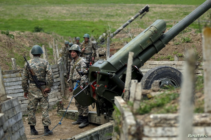 Ethnic Armenian soldiers stand next to a cannon at artillery positions near the Nagorno-Karabakh's town of Martuni, April 7, 2016.