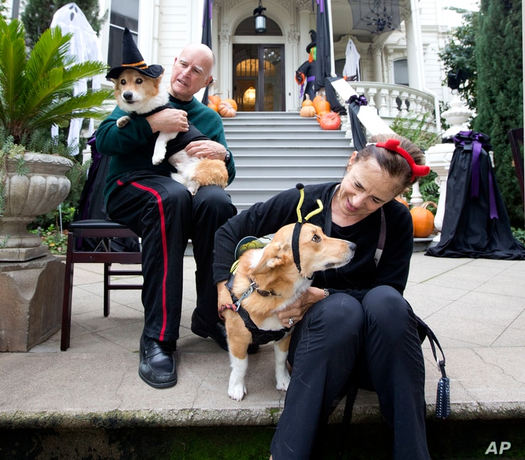 California Gov. Jerry Brown holds first dog, Sutter, as his wife, Anne Gust Brown holds deputy first dog, Colusa, as they wait for trick-or-treaters outside the Governor's Mansion in Sacramento, Calif., Oct. 31, 2016.