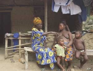 An expectant mother consults with a traditional birth attendant in Bonthe District. Most are not able to detect a problem pregnancy, or  intervene in an obstetric emergency.