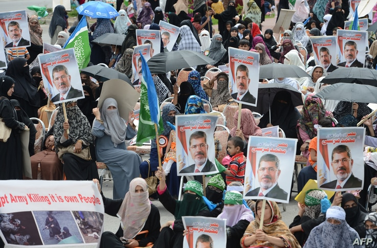 Women activists of Islamic political party Jamaat-e-Islami (JI) hold pictures of ousted Egyptian president Mohamed Morsi during a pro-Morsi rally in Islamabad on August 18, 2013.