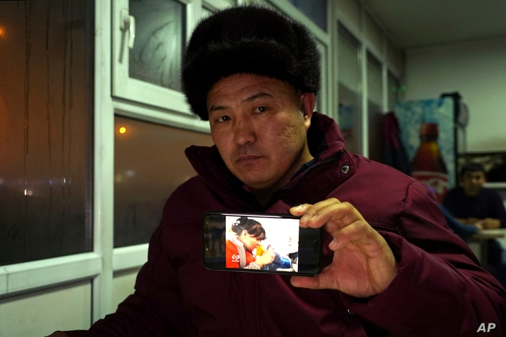 "In this Dec. 9, 2018, photo, Orynbek Koksebek, a former detainee in a Chinese internment camp, holds up a phone showing a state television report about what Beijing calls ""vocational training centers"" for a photo in a restaurant in Almaty, Kazakhstan..."
