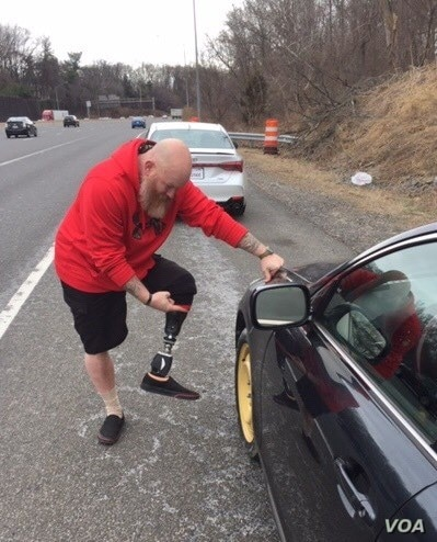 Afghanistan war veteran Anthony Maggert, helps General Colin Powell change a flat tire on his way to Walter Reed Military hospital in this photo posted by Gen. Colin Powell on his Facebook page.