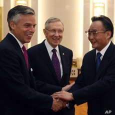 U.S. Senator Harry Reid (D-NV) looks on as U.S. ambassador to China Jon Huntsman (L) shakes hand with Wu Bangguo, chairman of the Standing Committee of the National People's Congress, at the Great Hall of the People in Beijing April 21, 2011