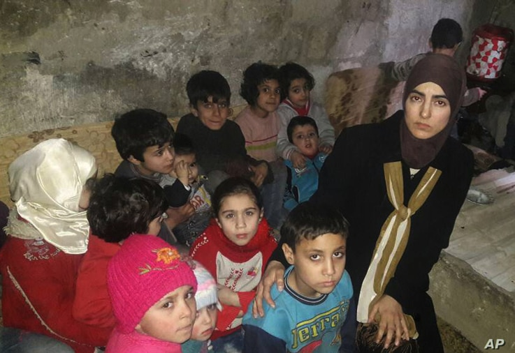 This March 11, 2018 photo, provided by Deana Lynn, from Detroit, Michigan, shows her, with her kids and other Syrian children at a shelter where they hide from Russian and Syrian government forces airstrikes, in eastern Ghouta, a suburb of the Syrian...