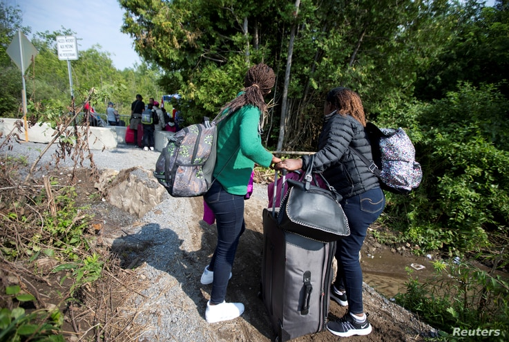 FILE - Women claiming to be from Burundi cross the U.S.-Canada border into Quebec from Champlain, New York, Aug. 3, 2017.