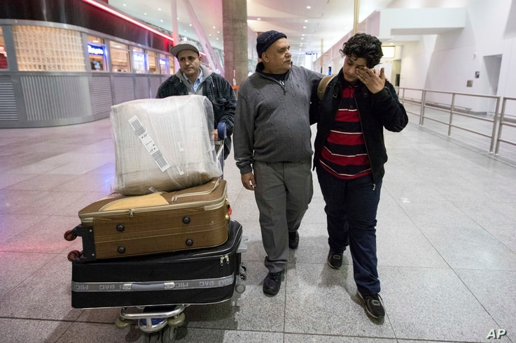 Ali Abdullah Alghazali, 13, right, from Yemen, wipes his eyes as he walks with his father Abdullah Alghazali, left, and his uncle after arrival at John F. Kennedy International Airport in New York, Feb. 5, 2017.