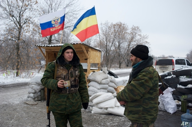 Pro-Russian rebels, cossacks from the 1st Cossack Regiment, guard a checkpoint decorated by Russian national and Don Cossacks flags, just outside in Pervomaisk, eastern Ukraine, Dec. 6, 2014.